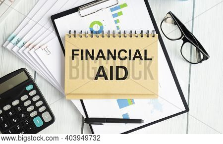 Financial Aid Text Written On A Notebook With Pencils And Calculator.
