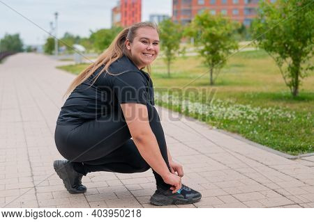 A Fat Woman In A Tracksuit Crouches Down And Ties Her Shoelaces Outdoors.