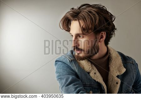 Men's beauty and hairstyle. Portrait of a handsome man with wavy dark hair and a beard on a gray background. Copy space.