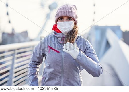 Adult woman jogging in the city in masks during lockdown