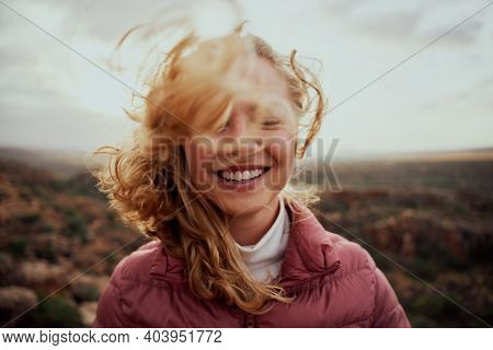 Portrait Of Young Smiling Woman Face Partially Covered With Flying Hair In Windy Day Standing At Mou