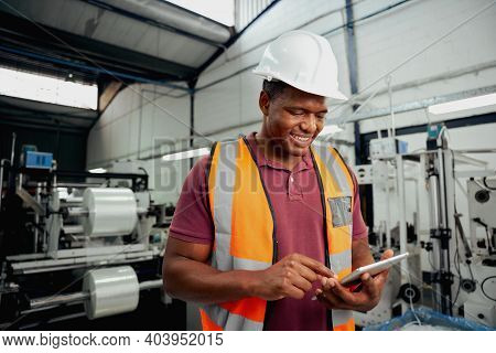 Happy Male Technician Engineer Checking Process On Digital Tablet In Large Factory