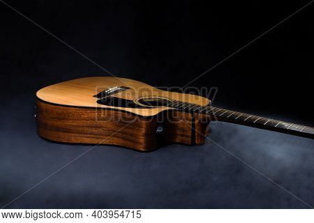 Classical Acoustic Guitar In Yellow With Black Pickguard On Isolated Black Background