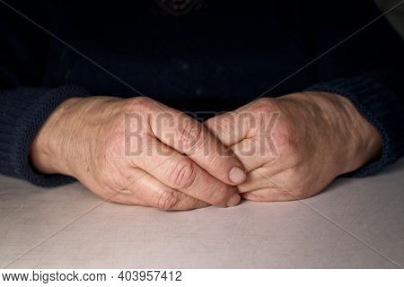 The Old Woman's Clasped Hands Lie On The Table. Wrinkles On The Hands. Loneliness Of The Elderly.