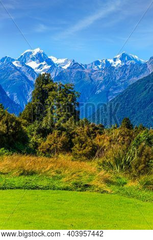 Great fields, forests and hills. The highest peak of New Zealand, Mount Cook and Mount Tasman is covered in snow and glaciers. South Island of New Zealand. Wonderful summer day