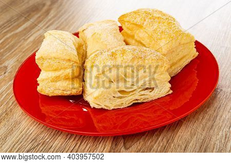 Few Puff Cookies In Red Glass Plate On Brown Wooden Table