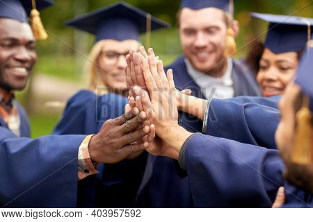 education, graduation and people concept - close up of happy international graduate students in mortar boards and bachelor gowns making high five