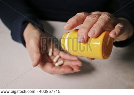 An Elderly Woman Pours Pills From A Jar Into Her Hand. Elderly Health Concept. Nursing And Caring Fo
