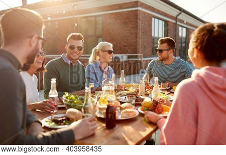 leisure and people concept - happy friends having dinner or barbecue party on rooftop in summer