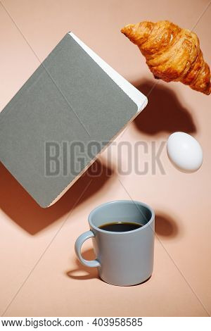 Breakfast Concept. Coffee Mug, Croissant, Egg And Notebook Hovering In Air
