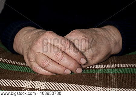 The Old Woman's Clasped Hands Lie On A Checkered Plaid. Wrinkles On The Hands. Loneliness Of The Eld
