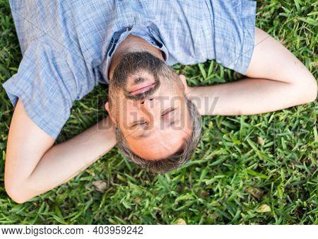 Adult caucasian man lying upside down portrait on grass
