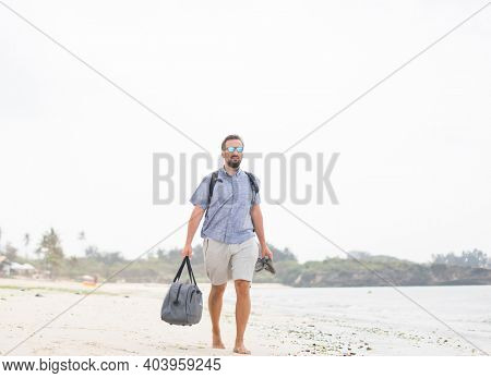 Cheerful adult man with bag having fun on the tropical beach