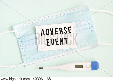 White Card With The Inscription Adverse Event On A Medical Protective Mask. Medical Concept.