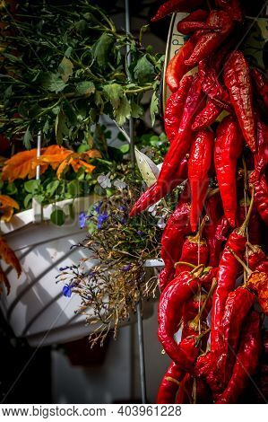 Hanging Strand Of Red Chili Peppers And Rustic Wall Decor