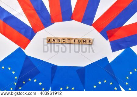 Concept Of Sanctions Between European Union And Russia. Eu Flags And Russian Flags On White Backgrou