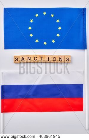Flags Of Russian And European Union. Word Sanctions Made Of Wooden Cubes.