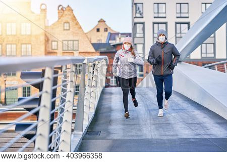 Adult couple jogging in the city in masks during lockdown