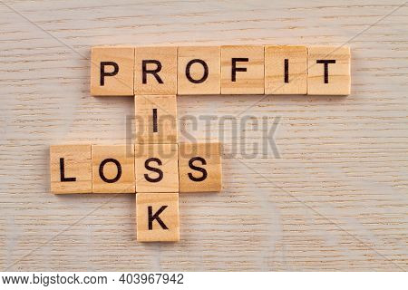 Puzzle With Economic Terms. Investment Is Always Risk. Profit And Loss Made With Wooden Blocks On Wo