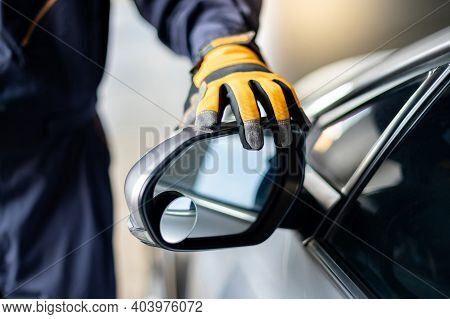 Male Auto Mechanic Hand Wearing Yellow Glove Adjusting Car Wing Mirror. Checking Car Part In Automot