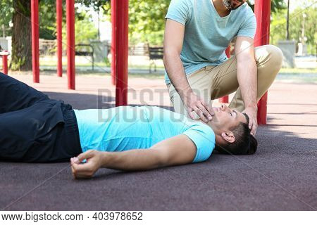 Passerby Giving First Aid To Unconscious Man Outdoors