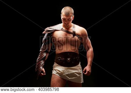 Gladiator With Sword And Armor On A Black Background. A Warrior In Gladiatorial Armor Looks Dawn At