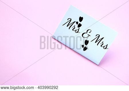White Paper Card With The Inscription Mrs And Mrs On A Pink Background. Lesbian Wedding