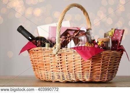 Wicker Basket With Gifts, Wine And Food Against Blurred Festive Lights. Space For Text