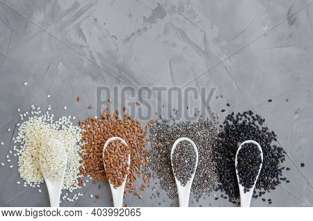 White Sesame Seeds, Flax Seeds, Chia, Black Sesame Seeds In Ceramic Spoons On A Gray Background. Hea