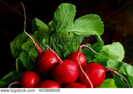 A Bunch Of Radishes With Green Leaves On A Dark Background