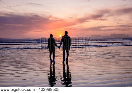 Couple Of Men And Women Mid-age Watching The Sunset On The Beach Of Tofino Vancouver Island Canada,