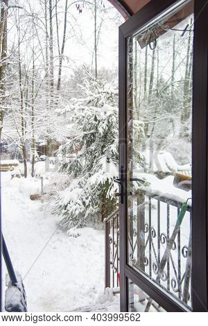 View Of The Snow-covered Courtyard Through The Open Door Of The Cottage.