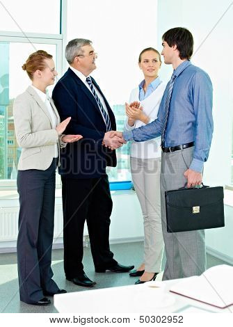 Photo of successful businessmen handshaking after striking deal with applauding women near by