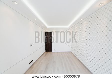 Modern empty room with a geometric pattern on the wall and lighting around the perimeter of the ceiling