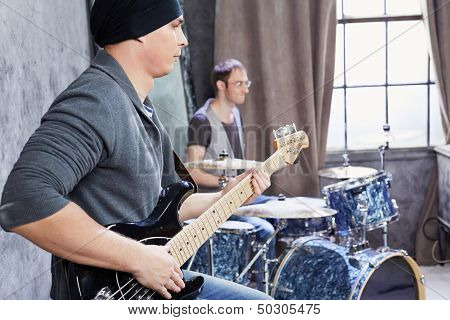 Bass guitarist and drummer play music