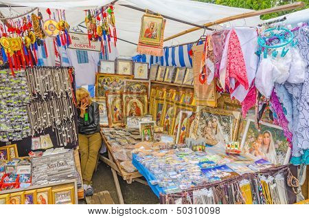 POCHAYIV, UKRAINE - AUGUST 14: Unidentified seller and the stand of religious articles in entrance of Holy Dormition Pochayiv Lavra, Pochayiv, Ukraine on August 14, 2013