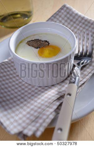Baked egg with sliced truffle in a ramekin