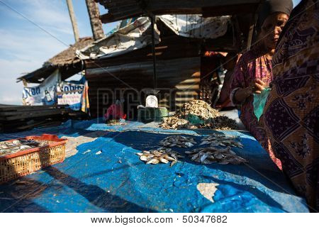 PADANG - AUGUST 25: A fishmonger attends to her customer at her stall at an outdoor market in Padang, West Sumatera, Indonesia on August 25, 2013. Resources from the sea is a major revenue earner.