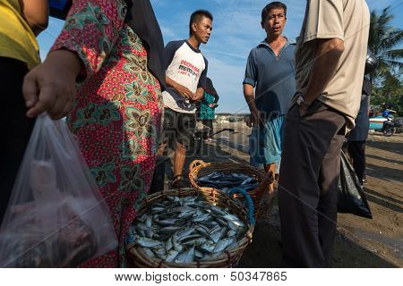 PADANG - AUGUST 25: Fishmongers negotiate fish price and trade at an outdoor village market in Padang, West Sumatera, Indonesia on August 25, 2013. Resources from the sea is a major revenue earner.