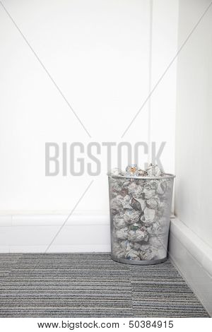 Wastebasket full of crumpled paper in corner against white wall