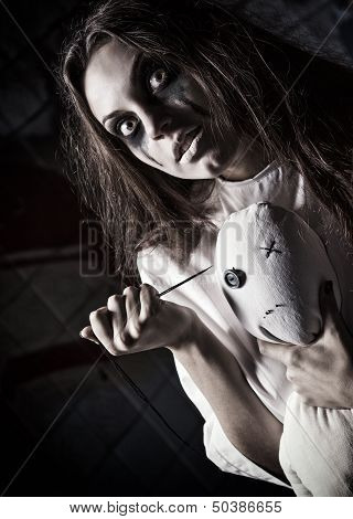 Horror Style Shot: Scary Mad Girl With Moppet Doll And Needle In Hands