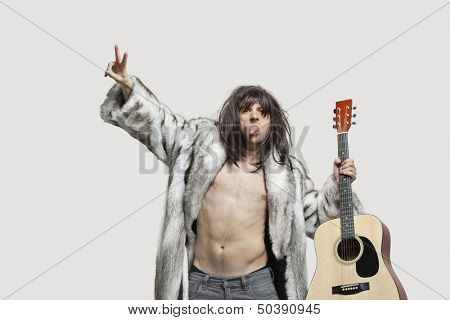 Young man in fur coat holding guitar while gesturing over gray background poster