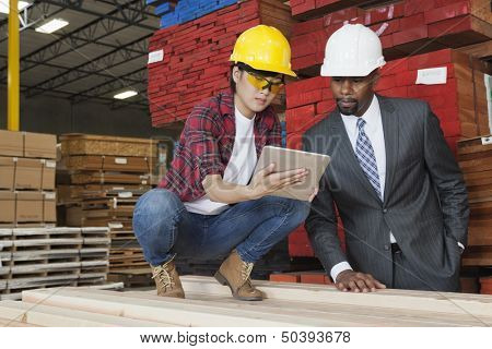 Female industrial worker showing something on tablet PC to male engineer