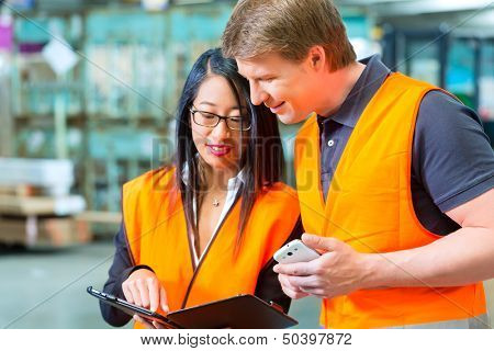 Logistics Teamwork - Worker or warehouseman and his female coworker with tablet computer at warehouse of freight forwarding company