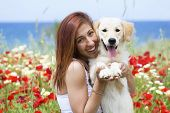 Happy young woman playing with dog on a meadow poster