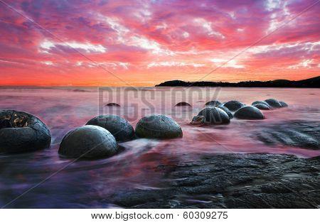 Moeraki Boulders on the Koekohe beach, Eastern coast of New Zealand. Sunset and long exposure