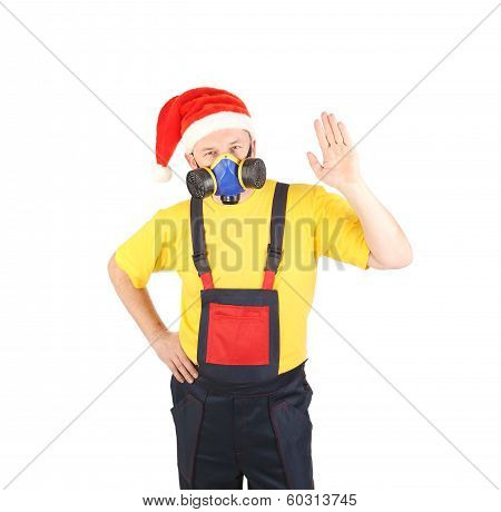 Worker in gas mask and santa hat say hi.