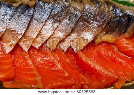 Smoked mackerel and trout cut on a platter closeup