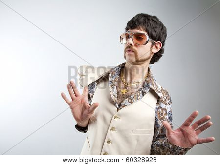 1970s retro man in a white leisure suite and sunglasses looking surprised