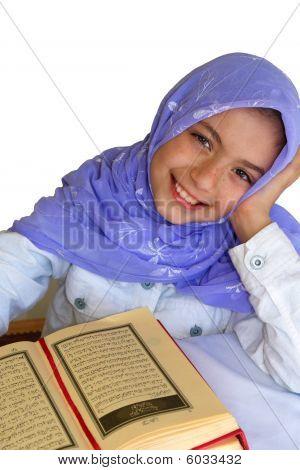 Little muslim girl in headscarf reads holy Koran poster